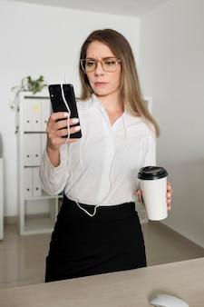 Mulher verificando o telefone no trabalho