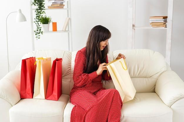 Mulher verificando os itens que recebeu durante as compras em liquidação