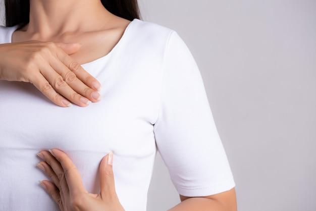 Mulher verificando protuberâncias no peito para sinais de câncer de mama.