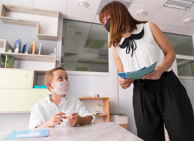 Mulher verificando seu aluno em sala de aula durante a pandemia