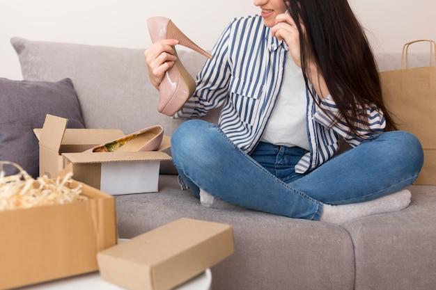 Mulher verificando seus sapatos novos enquanto está sentada no sofá