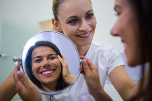 Mulher verificando sua pele no espelho depois de receber tratamento cosmético