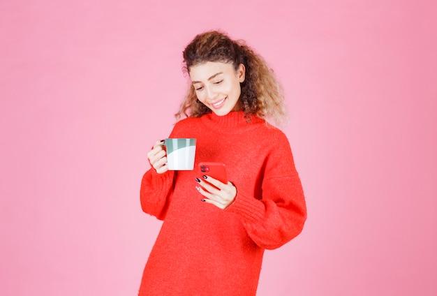 Mulher verificando suas mensagens enquanto bebe uma xícara de café.