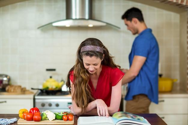 Mulher, verificar, a, receita, livro, em, cozinha, enquanto, homem, cozinhar, ligado, fogão, em, fundo