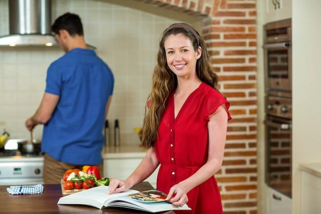 Mulher, verificar, a, receita, livro, em, cozinha, enquanto, homem, cozinhar, ligado, fogão