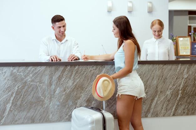 Mulher, verificar dentro, em, recepção hotel