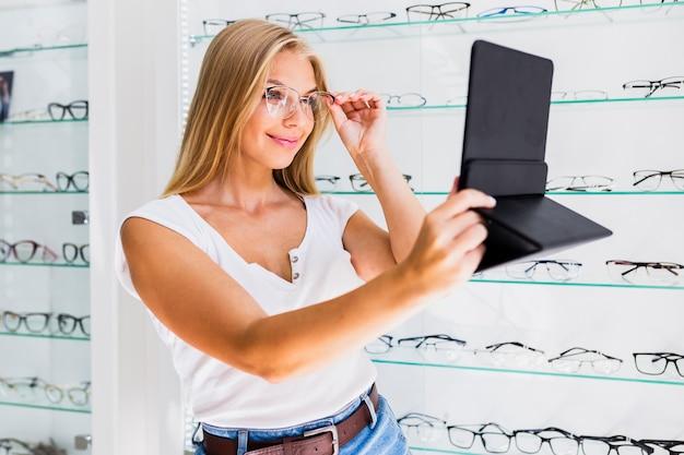 Mulher, verificar, óculos, quadro, em, espelho