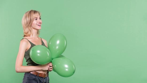 Mulher vestida casual, segurando balões
