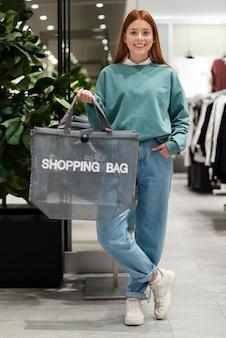 Mulher vestida casual, segurando o saco de compras