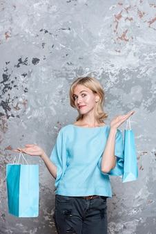 Mulher vestida casual, segurando sacos de papel