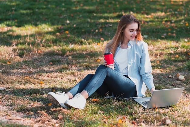 Mulher vestida casual, trabalhando no laptop na natureza