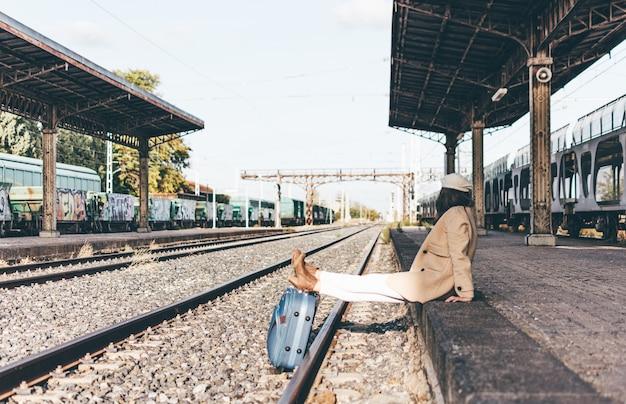 Mulher vestida com jaqueta bege e boina apoiada em uma mala em uma estação de trem