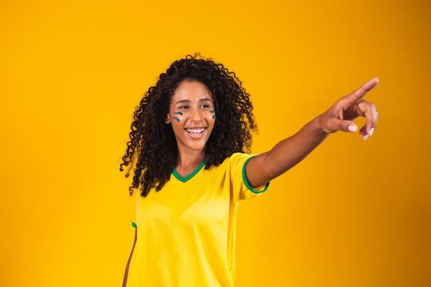 Mulher vestida com roupas brasileiras apontando para o horizonte