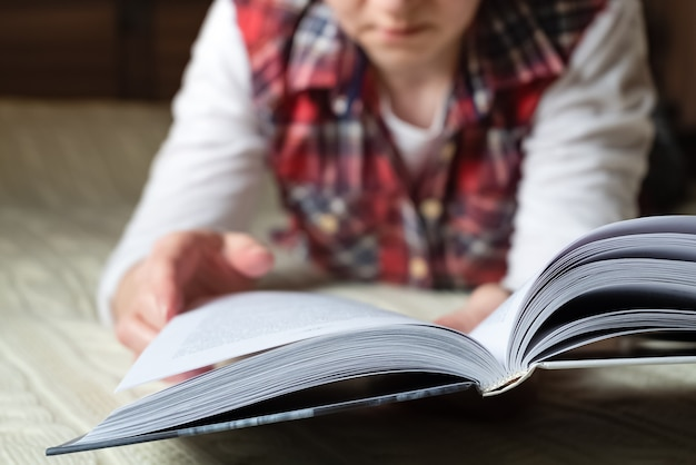 Mulher vestida com roupas casuais em casa deitada na cama lendo livro