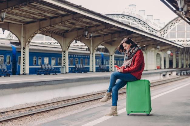 Mulher vestida com roupas casuais, senta-se na bagagem, mantém o telefone móvel, feliz em receber mensagem de texto, posa na plataforma