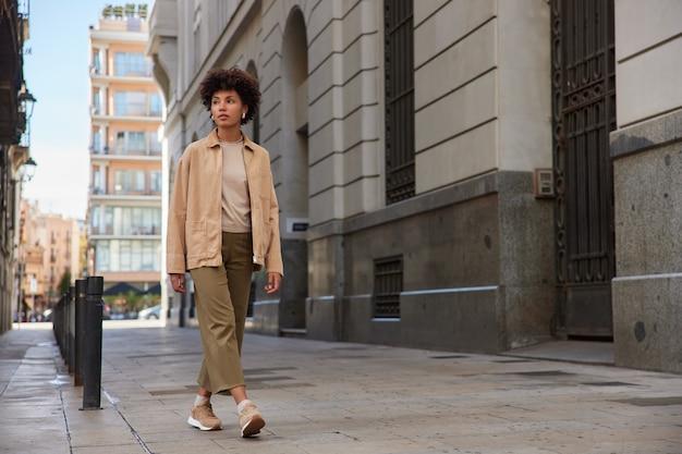 Mulher vestida com roupas da moda faz tour pela cidade durante os fins de semana olha para longe caminha no centro da cidade na calçada perto de edifícios antigos chega ao destino