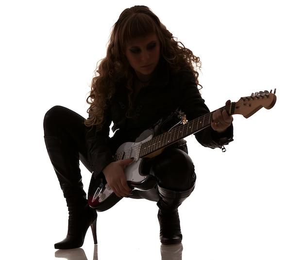 Mulher vestida com roupas de couro preto, agachada e segurando seu violão