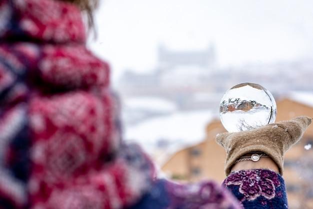Mulher vestida com roupas de inverno, segurando uma bola de cristal em uma paisagem urbana de neve.