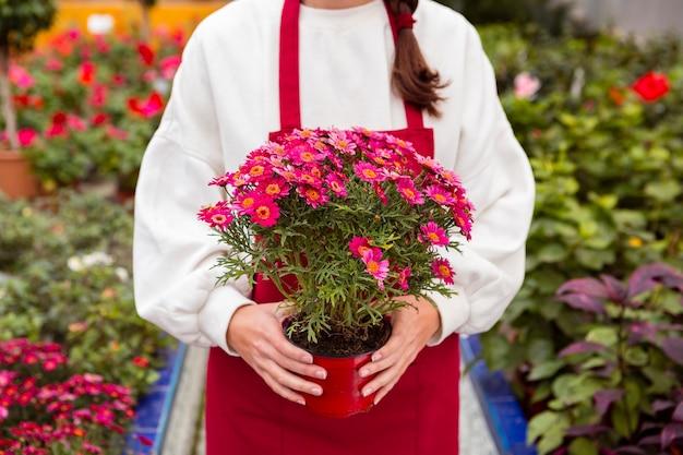 Mulher vestida com roupas de jardinagem, segurando o vaso de flores