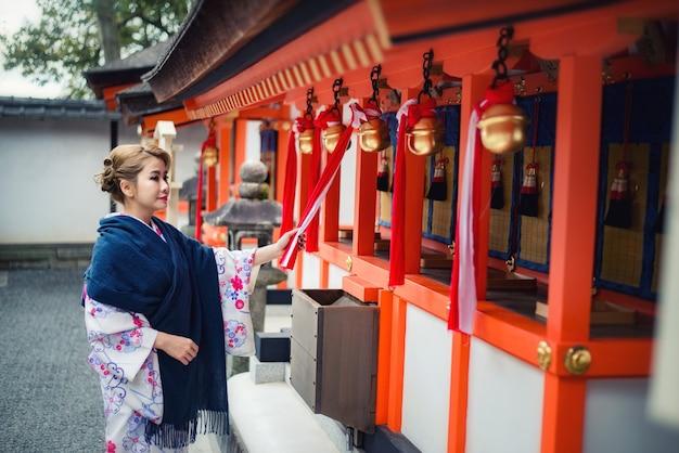 Mulher vestida com traje tradicional japonês passando sob os portões tori no santuário fushimi-inari, kyoto, japão