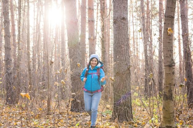 Mulher vestida com um casaco azul, caminhando na floresta.