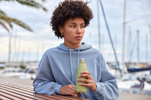 Mulher vestida com um moletom confortável bebe hidratos de água depois de atravessar o porto marítimo e parece estar sonhando acordada com alguma coisa