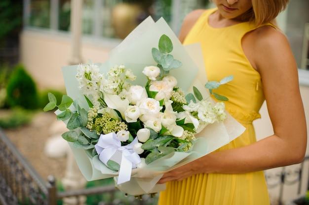 Mulher vestida com um vestido amarelo, segurando um buquê de flores branco