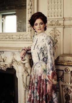Mulher vestida com um vestido no palácio posando ao lado da lareira