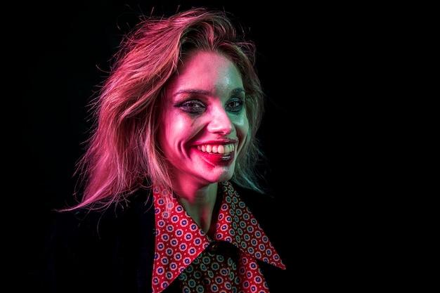 Mulher vestida como palhaço sorrindo com os dentes