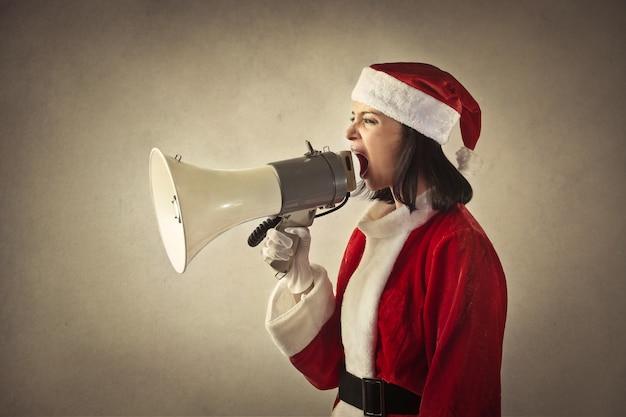 Mulher vestida como santa gritando em um megafone