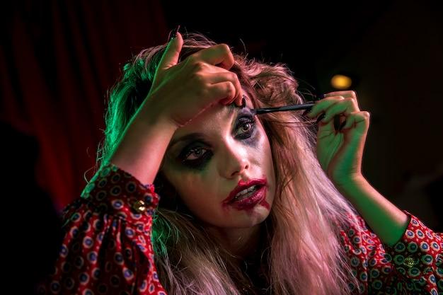Mulher vestida como um palhaço usando maquiagem