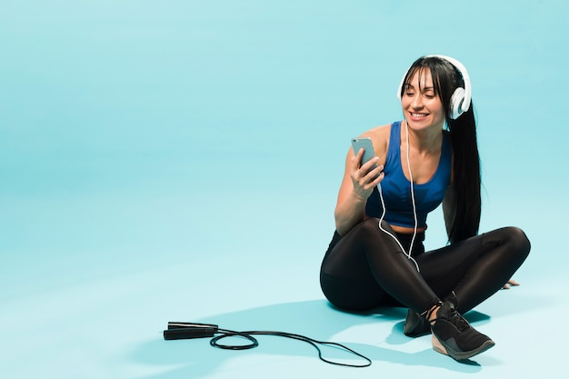 Mulher vestida de academia, curtindo música em fones de ouvido com pular corda