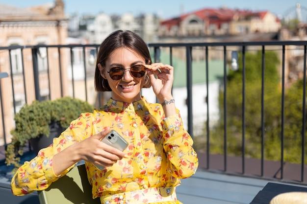 Mulher vestida de amarelo no terraço de um café de verão com telefone celular em um dia de sol, parece feliz e positiva com um enorme sorriso no rosto