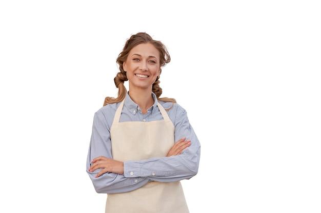 Mulher vestida de avental branco com parede branca proprietária de empresa de meia-idade em uniforme