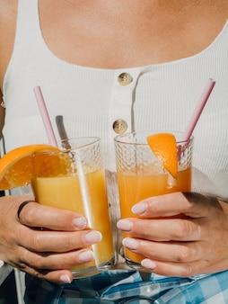 Mulher vestida de branco, segurando copos de suco