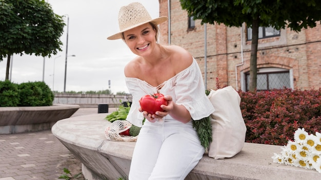 Mulher vestida de branco segurando um tomate fresco