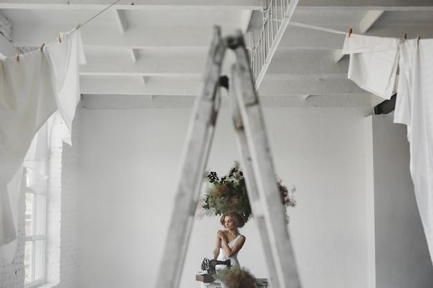 Mulher vestida de branco senta-se em uma sala com flores e máquina de costura