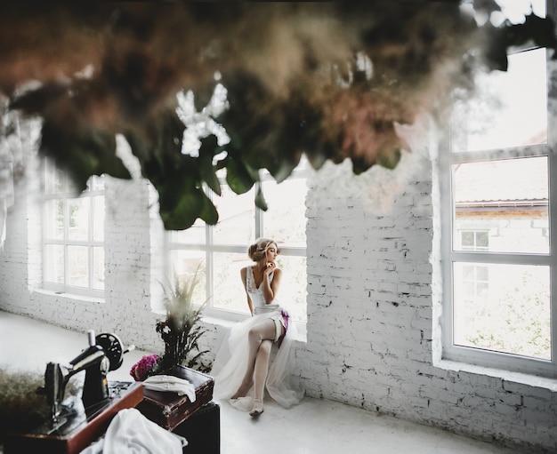 Mulher vestida de branco senta-se no peitoril da janela em uma sala com flores e máquina de costura