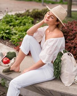 Mulher vestida de branco sentada ao lado de vegetais