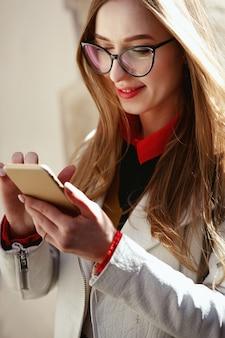 Mulher vestida de estilo casual verifica seu telefone em pé na rua