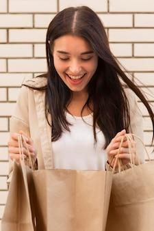 Mulher vestida de forma elegante olhando para sacolas de compras