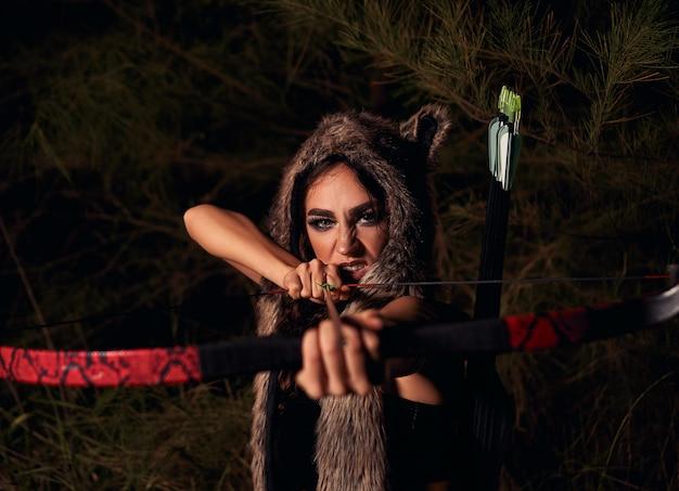 Mulher vestida de lobo atirando flecha