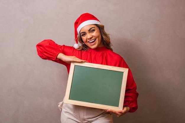 Mulher vestida de mama claus segurando uma lousa com espaço livre para texto.