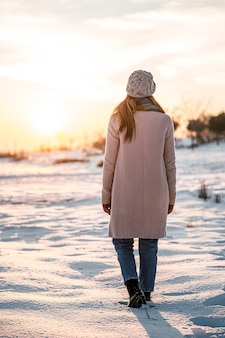 Mulher vestida de quente sozinha entre um prado nevado admirando o pitoresco pôr do sol no campo
