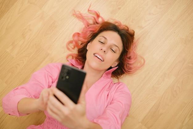 Mulher vestida de rosa deitada no chão usando seu telefone celular