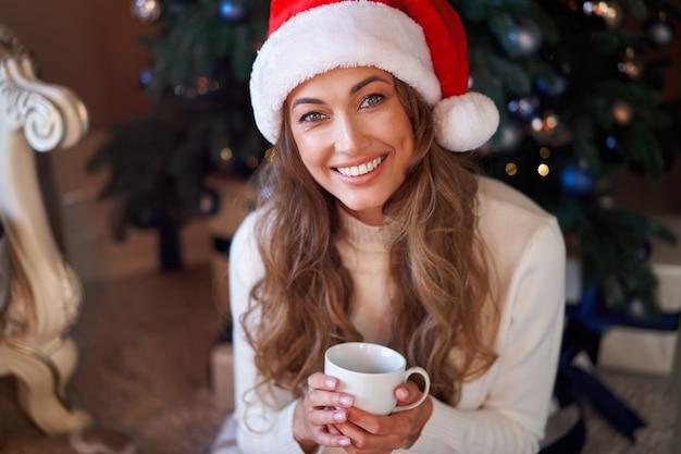 Mulher vestida de suéter branco com chapéu de papai noel e calça jeans sentada no chão perto da árvore de natal com caixa de presente