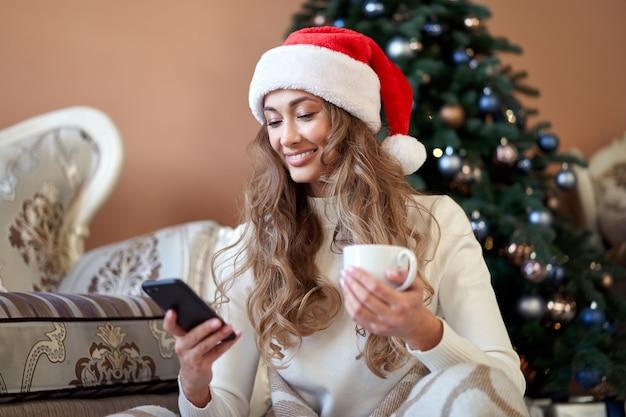 Mulher vestida de suéter branco com chapéu de papai noel no chão perto da árvore de natal com smartpone e uma xícara de café