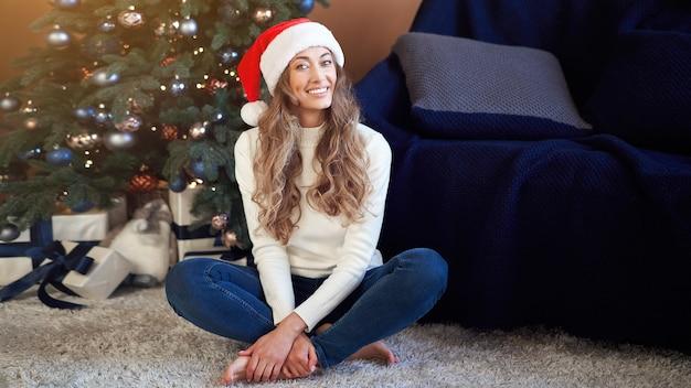 Mulher vestida de suéter branco e calça jeans sentada no chão perto da árvore de natal com uma caixa de presente