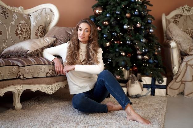 Mulher vestida de suéter branco e calça jeans sentada no chão perto da árvore de natal