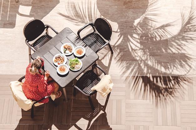 Mulher vestida de vermelho se senta a uma mesa ao sol, sob a sombra das palmeiras. vista do topo